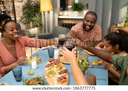 Happy young woman and her father clinking with glasses of wine over served table Stock photo © pressmaster