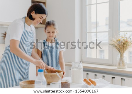 Photo of brunette woman in striped apron, mixes ingredients with beater, shows small daughter how to Stock photo © vkstudio
