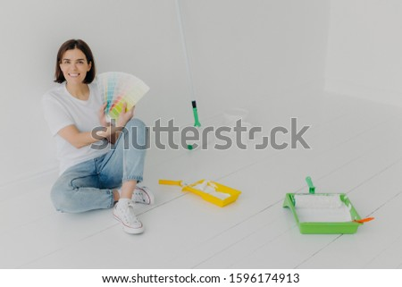 Glad brunette woman demonstrates color samples, dressed in white t shirt and jeans, chooses tone for Stock photo © vkstudio