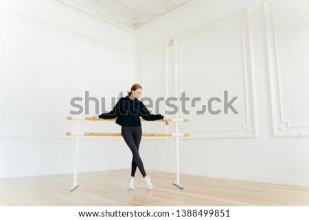 Classic ballet dancer has stretching workout, stands near ballet barres, wears black sweatshirt and  Stock photo © vkstudio
