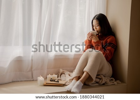Young girl with cup of hot beverage and candles sitting on the s Stock photo © dashapetrenko