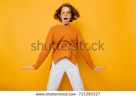 Cute casual young woman fooling around in front of yellow wall Stock photo © boggy