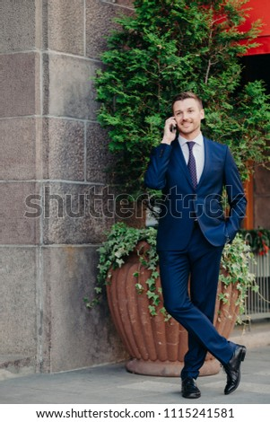 Clever handsome male manager in formal clothes, shares good news with business partner, being glad a Stock photo © vkstudio