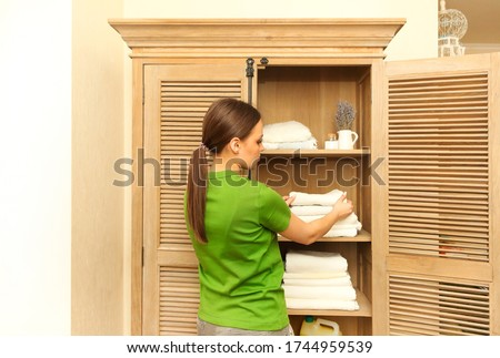 Young woman wearing green t-shirt near cupboard holding towels i Stock photo © dashapetrenko