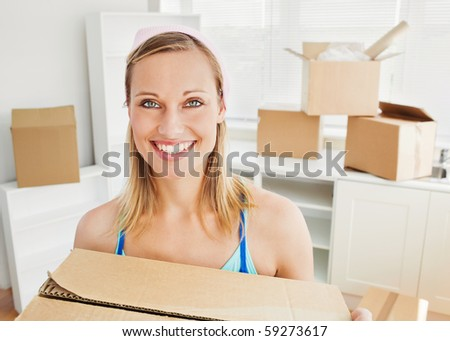 Smiling woman holding boxes after moving looking at the camera Stock photo © HASLOO