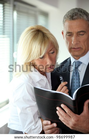 mature businessman consulting his agenda with blonde secretary by his side Stock photo © photography33