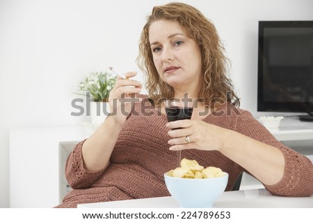 woman smoking cigarette whilst drinking wine and eating snacks stock photo © highwaystarz