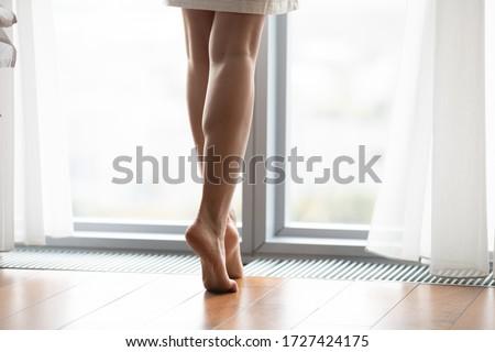 Beautiful slim legs of woman standing barefoot on wooden floor Stock photo © deandrobot