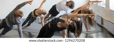 Male instructor with student practicing side plank pose in yoga studio Stock photo © wavebreak_media