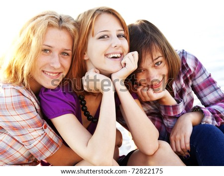 Stock photo: Portrait of three beautiful girls. With counter light on backgro
