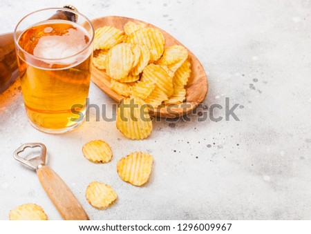 Glass of craft lager beer with snack and opener on stone kitchen Stock photo © DenisMArt