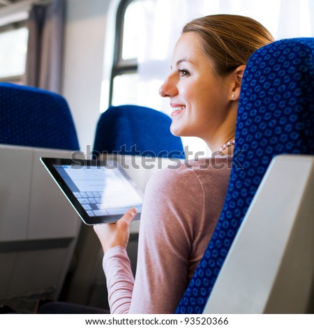 Young woman using her tablet computer while traveling by train. Travel application concept Stock photo © artfotodima