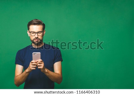 happy young man isolated over beige background using phone listening music by earphones singing stock photo © deandrobot