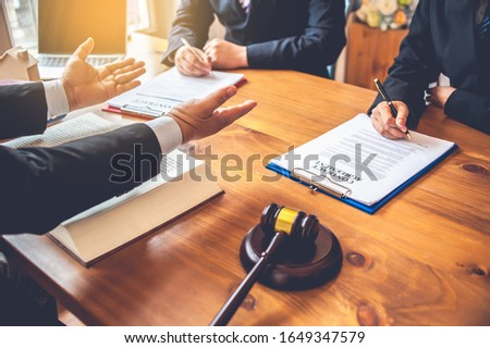 business people and lawyers discussing contract papers sitting a stock photo © snowing