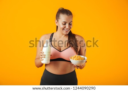 Image of sporty chubby woman in tracksuit holding milk and corn  Stock photo © deandrobot