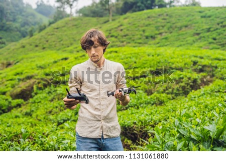 Men tourist tries to launch the drone at a tea plantation. Natural selected, Fresh tea leaves in tea Stock photo © galitskaya