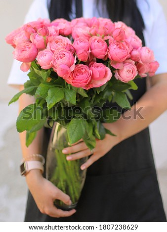 Young woman with a big vase of roses flowers in a color of the year 2019 Living Coral Pantone on a g Stock photo © artjazz