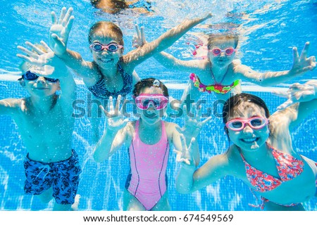 a child boy is swimming underwater in a pool smiling and holding breath with swimming glasses stock photo © galitskaya