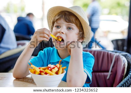 cute healthy preschool kid boy eats french fries potatoes with ketchup with his mom child eating un stock photo © galitskaya
