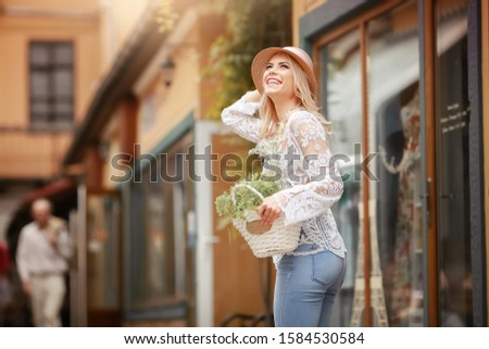 Lovely young lady in summer hat resting in open-air cafe propped face with hand and waiting friend.  stock photo © ElenaBatkova
