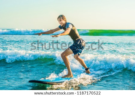 Young man, beginner Surfer learns to surf on a sea foam on the Bali island BANNER, long format Stock photo © galitskaya