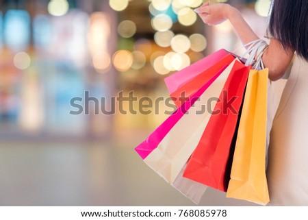 Women carrying a lot of shopping bags in blurred shopping mall Stock photo © galitskaya