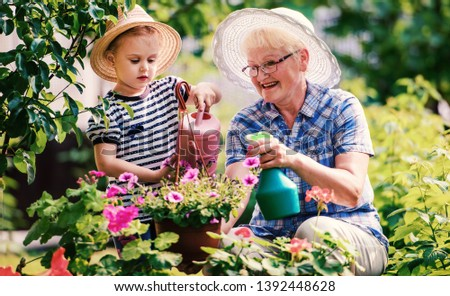 Grandmother and her grandchild enjoying in the garden with flowe Stock photo © boggy