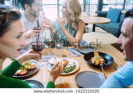 friends in a restaurant having a jolly good time enjoying the food stock photo © kzenon