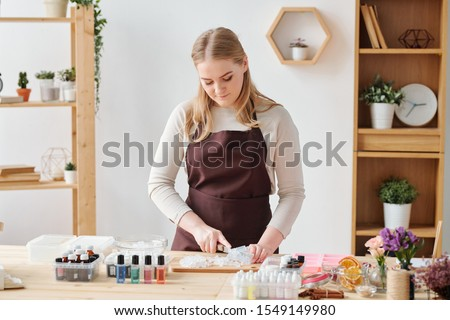 Craftswoman in brown apron preparing hard soap mass for further treatment Stock photo © pressmaster
