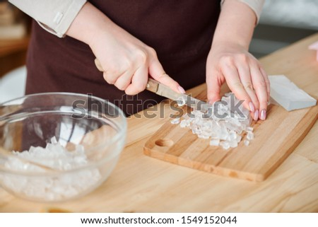 Hands of young craftswoman with knife cutting transparent soap mass on board Stock photo © pressmaster