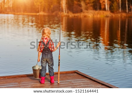 Fisherman sitting with a fishing rod on the bridge on the river Stock photo © barsrsind