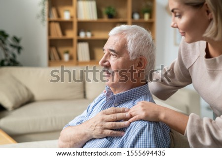 Sick retired man with grey hair holding hand of his young careful daughter Stock photo © pressmaster