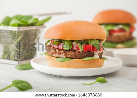 Healthy vegetarian meat free burger on round ceramic plate with vegetables and spinach on light tabl Stock photo © DenisMArt