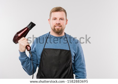Happy young hairdresser in apron and pullover holding hairdryer while working Stock photo © pressmaster
