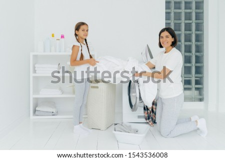 Glad housewife does washing with little adorable helper. Mother and daughter wash clothes in laundry Stock photo © vkstudio