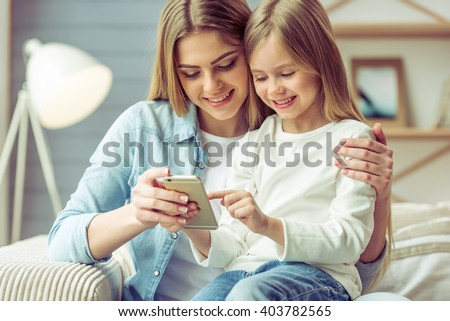 Happy caring woman embraces her little daughter, sit on washing machine, have rest after washing, su Stock photo © vkstudio