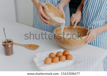 Unrecognizable mother and daughter add milk in bowl, make dough, homemade cookies wear aprons, stand Stock photo © vkstudio