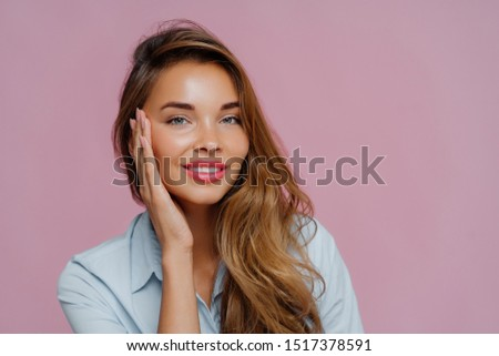 Photo of pleasant looking female model touches cheeks with palm, has gentle toothy smile, wears make Stock photo © vkstudio