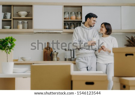 Indoor shot of lovely newlywed couple talk to each other with pleased expressions, drink takeaway co Stock photo © vkstudio
