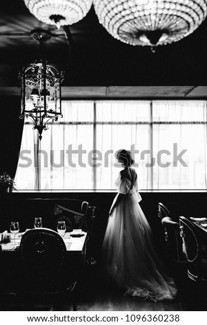 A bride in a wedding dress stands with her back to the camera under a tree Stock photo © ElenaBatkova