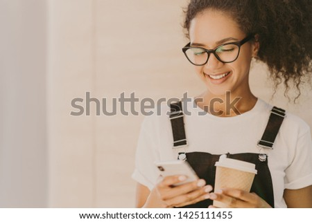 Adorable teeange girl with curly hair, checks news feed, messages in social networks, uses free inte Stock photo © vkstudio