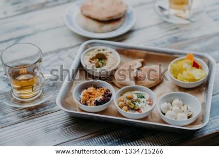Overhead image of traditional Israel food on tray. Hummus, domestic goat cheese, tomatoe core, beetr Stock photo © vkstudio