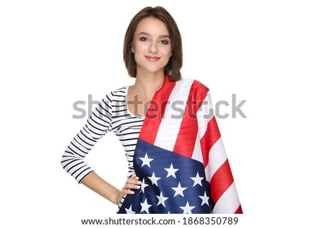 Portrait of young Caucasian woman wrapped in an american flag at beach. She is smiling and looking a Stock photo © wavebreak_media