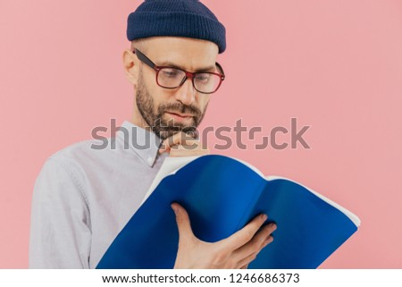 Close up shot of serious man holds chin, has dark stubble, wears glasses for good vision, carries op Stock photo © vkstudio