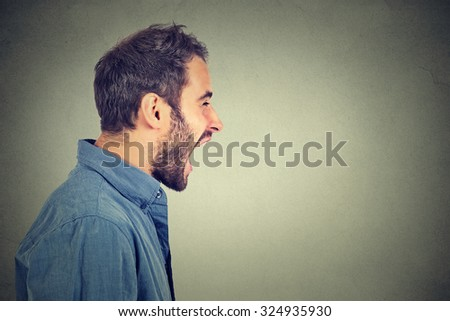 Young angry man shouting and screaming loud to side with hand on mouth and copy space for text over  Stock photo © GVS