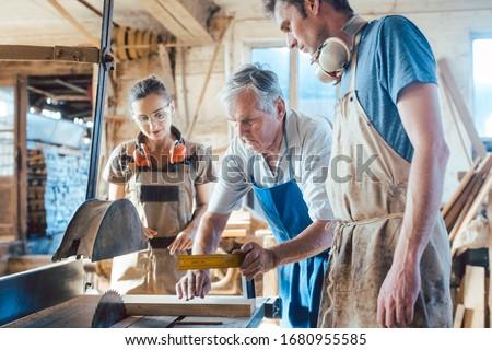 Experienced master carpenter transferring knowledge to his colleagues Stock photo © Kzenon