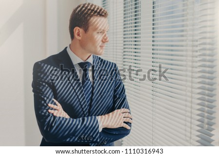 Contemplative male director keeps arms folded, thinks about future work plans, dreams about high pro Stock photo © vkstudio