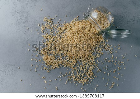 Horizontal shot of sprouted green buckwheat spilled from glass jar. Uncooked germinated seeds for di Stock photo © vkstudio