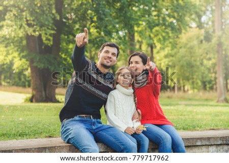 Father and mother sit between their daughter against trees or na Stock photo © vkstudio