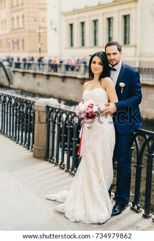 Handsome bearded bridegroom embraces his bride in white dress with bouquet stand together at bridge, Stock photo © vkstudio